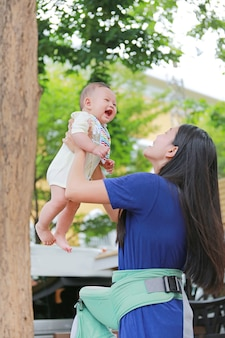 Happy asian mother throws up her infant in arms at garden.