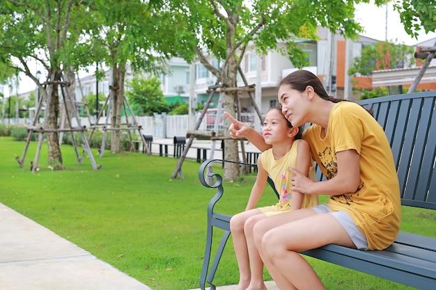 Счастливые азиатские мама и дочь расслабляясь, сидя на скамейке в саду на открытом воздухе. мать указывая что-то с детской девушкой, глядя в летний парк.