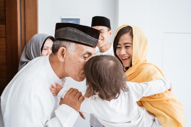 Счастливая азиатская мусульманская пожилая пара встречает детей и внуков на пороге во время празднования ид мубарак