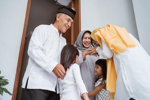 Happy asian muslim aged couple meeting kids and grand children at doorstep during eid mubarak celebration