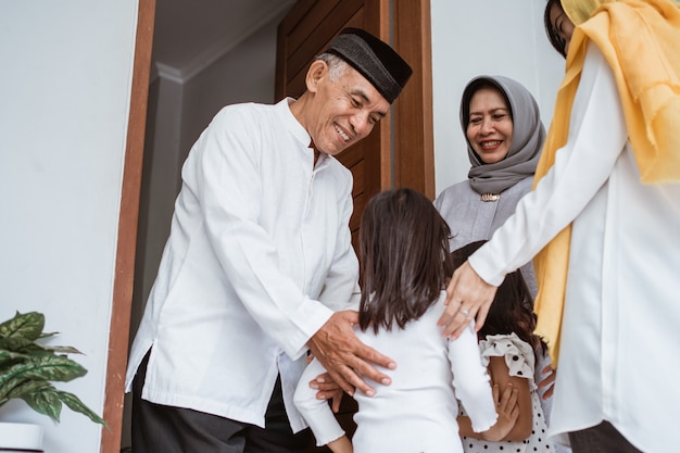 Happy asian muslim aged couple meeting kids and grand children at doorstep during eid mubarak celebration