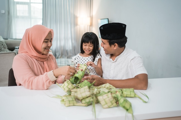 一起制作ketupat的愉快的亚洲穆斯林家庭在家在Eid穆巴拉克前