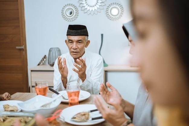 Счастливая азиатская мусульманская семья молится перед едой ифтар во время поста в рамадан