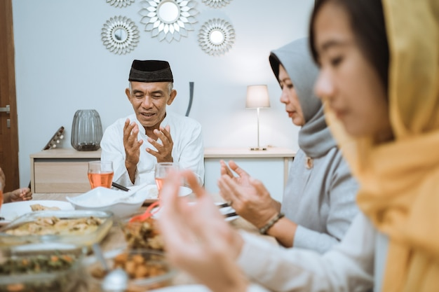 Happy asian muslim family praying before having their iftar meal during ramadan fasting