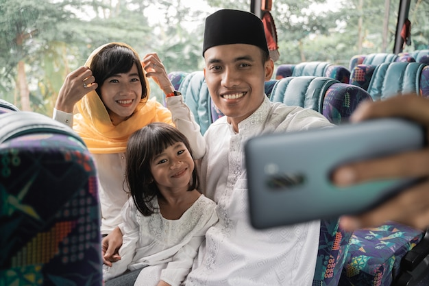 家族と一緒にバスに乗って幸せなアジアのイスラム教徒の休日の旅行