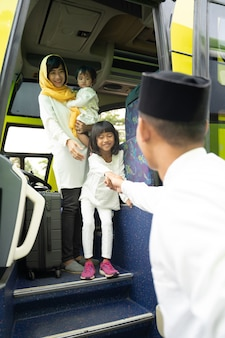 Happy asian muslim holiday trip riding a bus together with family wearing mask preventing virus spread