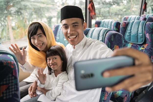 Happy asian muslim holiday trip riding a bus together with family