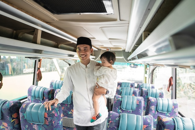 Happy asian muslim man and daughter doing eid mubarak traveling back to his hometown by riding a bus