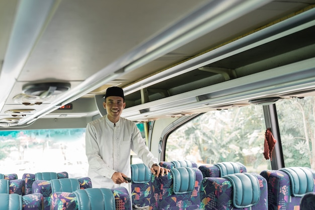 Happy asian muslim man doing eid mubarak traveling back to his hometown by riding a bus