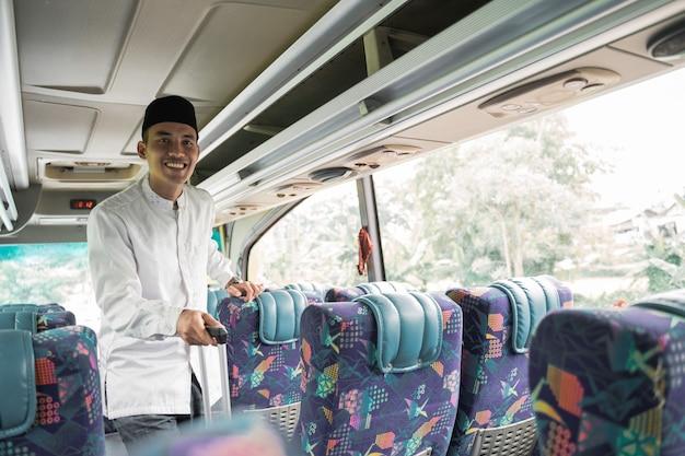 バスに乗って故郷に戻るイードムバラクをやって幸せなアジアのイスラム教徒の男