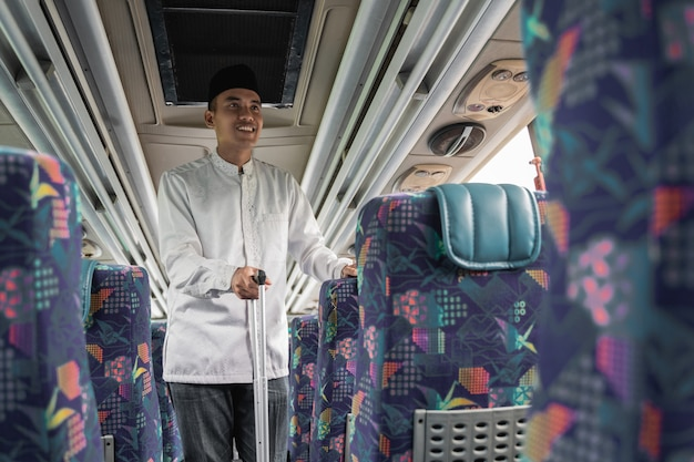Happy asian muslim man doing traveling back to his hometown by riding a bus