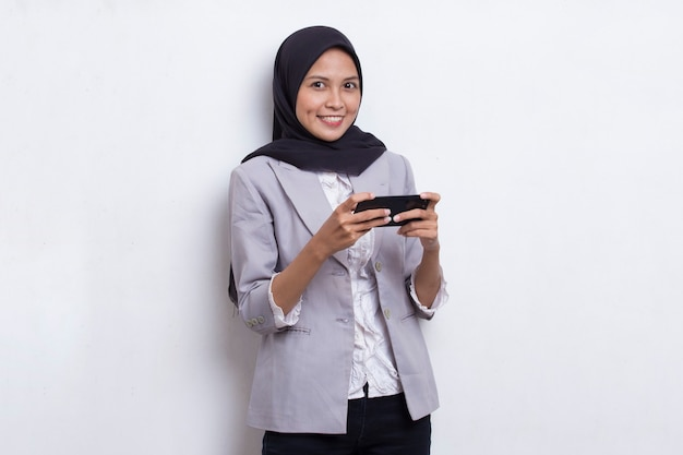 Happy asian muslim woman excited to play games on her smart phone
