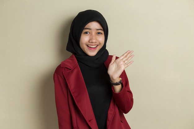 Happy asian muslim woman say hello on gray background