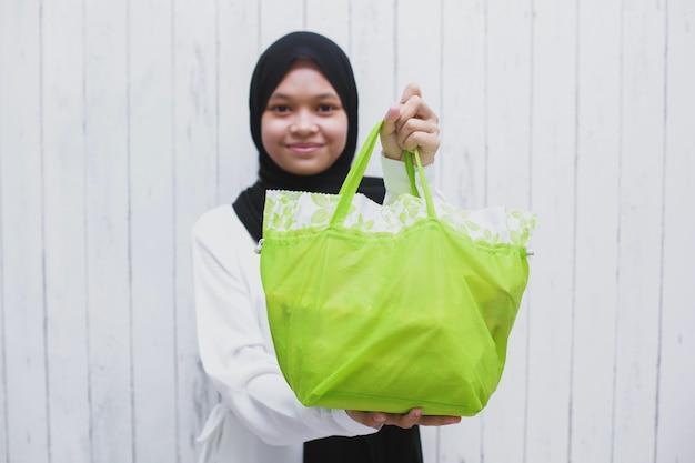 Счастливая азиатская мусульманская женщина показывает и дарит подарки в зеленой сумке