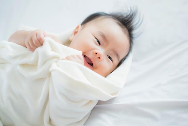 幸せなアジアの生まれたばかりの赤ちゃんのクローズアップ