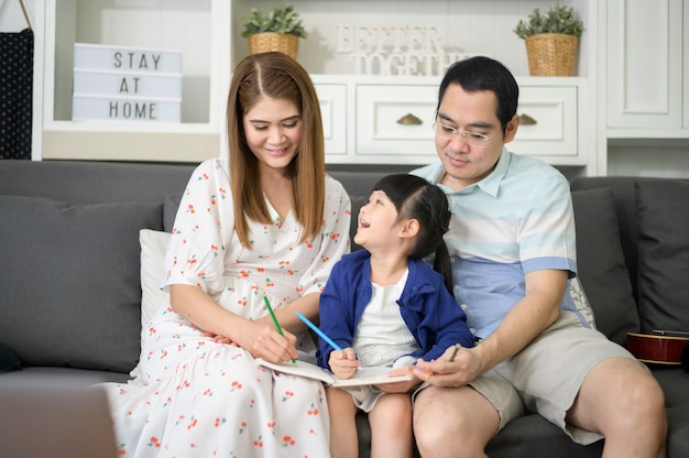 Premium Photo | Happy asian parent teaching little cute daughter to do  homework and drawing picture together at home.