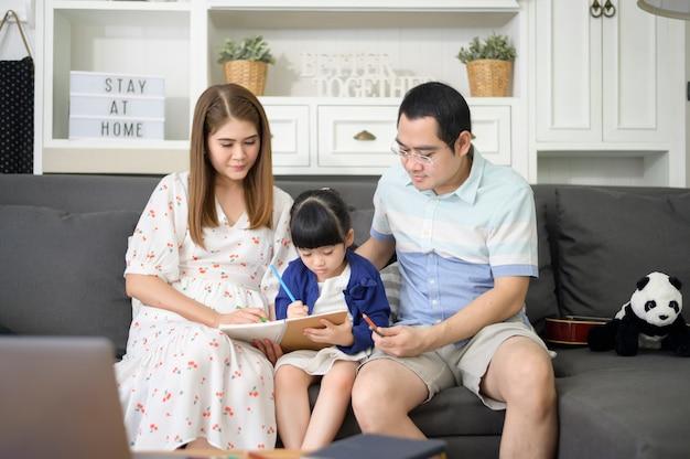 宿題をするかわいい娘を教えて、家で一緒に絵を描く幸せなアジアの親。