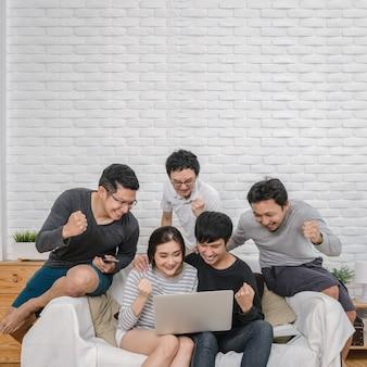 Счастливый группы азиатских людей, сидя и используя цифровой ноутбук в веселой и праздничной акции