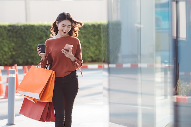 Happy asian pretty girl holding shopping bags