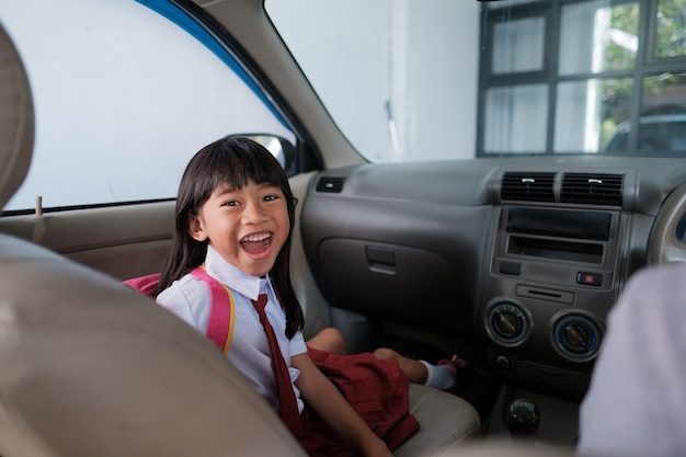Happy asian primary student while going to school by car with parent in the morning