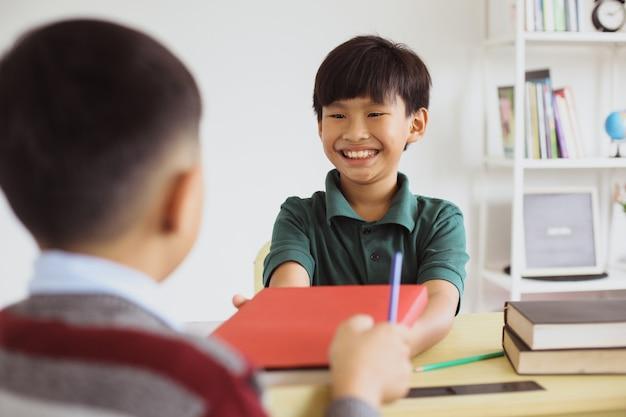幸せなアジアの男子生徒が教室で交流