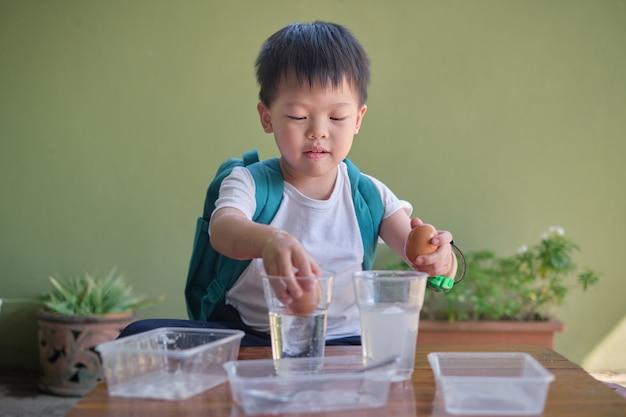 楽しくて簡単な浮遊卵科学実験をやって科学を勉強している幸せなアジアの学校の子供