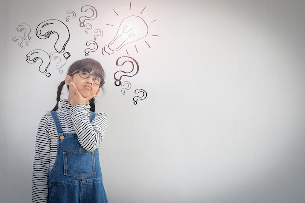 Happy asian school kid thinking