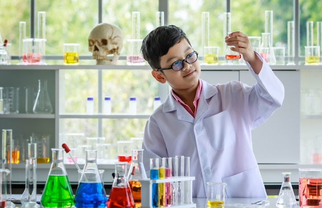 Happy asian schoolboy in white lab coat and glasses looking at glass flask with colorful liquid while analyzing results of scientific experiment in chemistry laboratory.