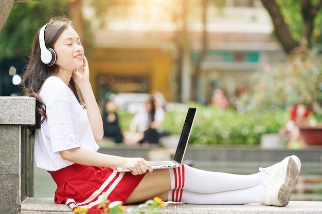 ラップトップでキャンパスに座って、後ろに寄りかかって、ヘッドフォンで美しい音楽を聴いている制服を着た幸せなアジアの女子高生