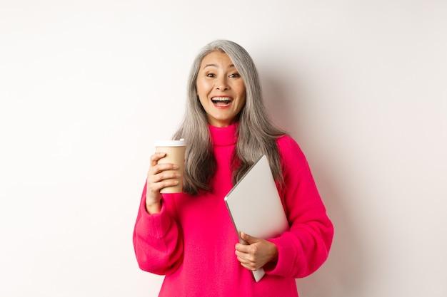 笑って、コーヒーを飲み、ラップトップを持って、白地にピンクのセーターに立って幸せなアジアのシニア女性起業家