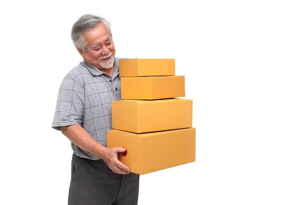 白い壁、配達宅配便および配送サービスのコンセプトに分離されたパッケージ宅配ボックスを保持している幸せなアジアシニア男