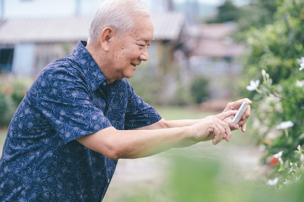 携帯電話で写真を撮る学年の幸せなアジアの年配の男性。幸せな退職後の生活。