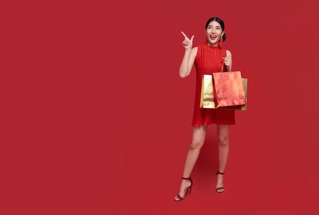 Счастливая азиатская шопоголическая женщина в традиционном платье чонсам ципао рука указывает на копирование пространства