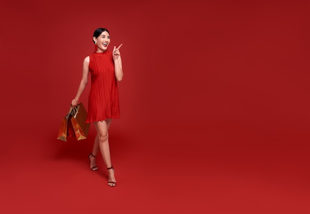 Happy asian shopaholic woman wearing traditional cheongsam qipao dress hand pointing up to copy space isolated on red background. happy chinese new year
