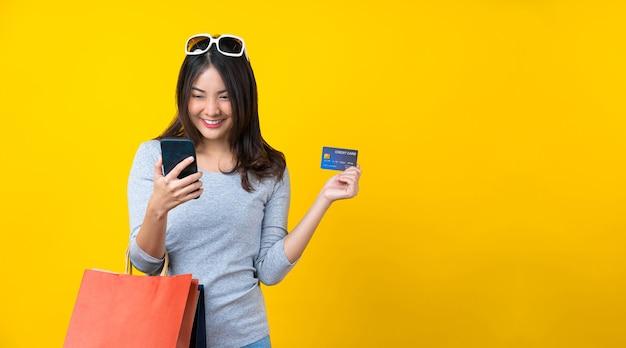 Счастливая азиатская улыбающаяся женщина, использующая мобильный телефон и кредитную карту и совершающая покупки