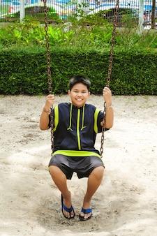 Счастливый азиатский спортивный мальчик играет на качелях в саду.