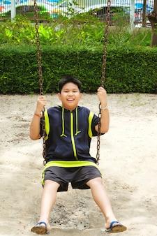 幸せなアジアのスポーツ少年が庭でスイングの遊び場で遊ぶ。