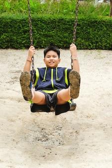 행복 한 아시아 스포츠 소년 정원에서 그네 놀이터에서 재생합니다.