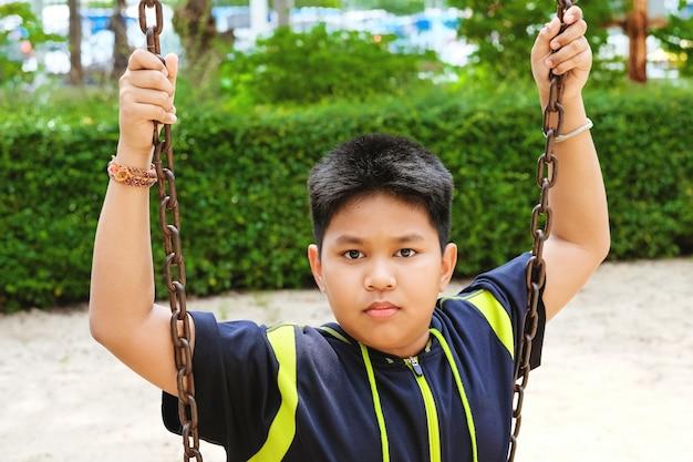Happy asian sport boy play on swing playground in garden.