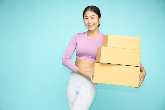 Happy asian sporty woman  holding package parcel box isolated on green background