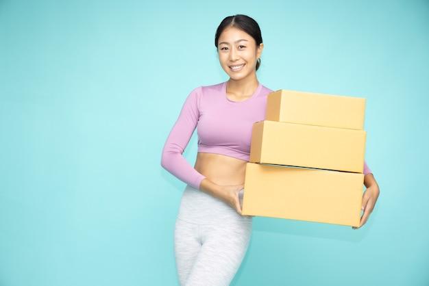 녹색 배경에 고립 된 패키지 소포 상자를 들고 행복 한 아시아 스포티 한 여자