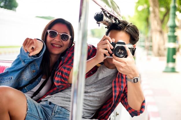 Happy asian tourist couple traveling on tuk tuk taxi in bangkok thailand