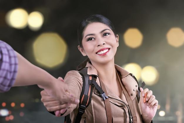 Happy asian tourist woman follow the husband hand