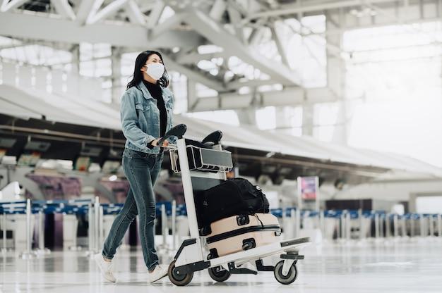 荷物台車で歩くマスクを持つ幸せなアジアの観光客の女性