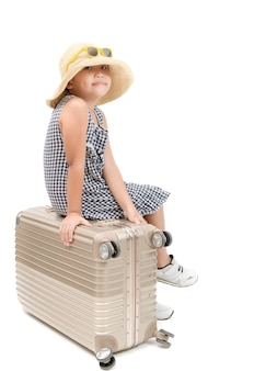Happy asian traveler sit on baggage isolated on
