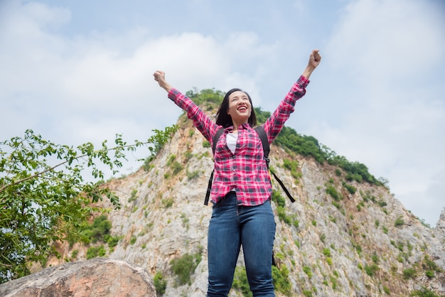 Happy asian traveller woman with backpack standing at stone hill  and smiles with raising hands. summer holiday and vacation trip , survival travel, lifestyle concept.