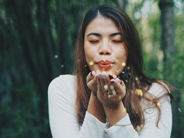 Счастливый азии женщина, дует золотой блеск.