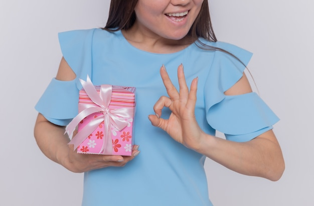 Happy asian woman in blue dress holding present showing ok sign smiling celebrating international women's day standing over white wall