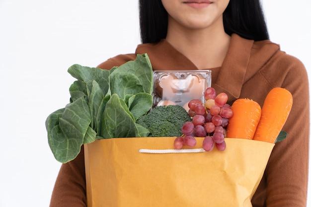幸せなアジアの女性は食料品店から宅配便の後に買い物紙袋を運ぶ