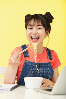 Happy asian woman carrying instant noodles with chopsticks to mouth, in front of laptop